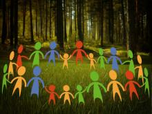 multicolored figures form a circle in a forest clearing